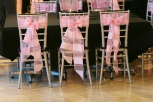three chairs in a row with a big pink bow tied behind them for an event